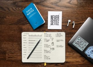 notebook with planning tasks, pc and earphones
