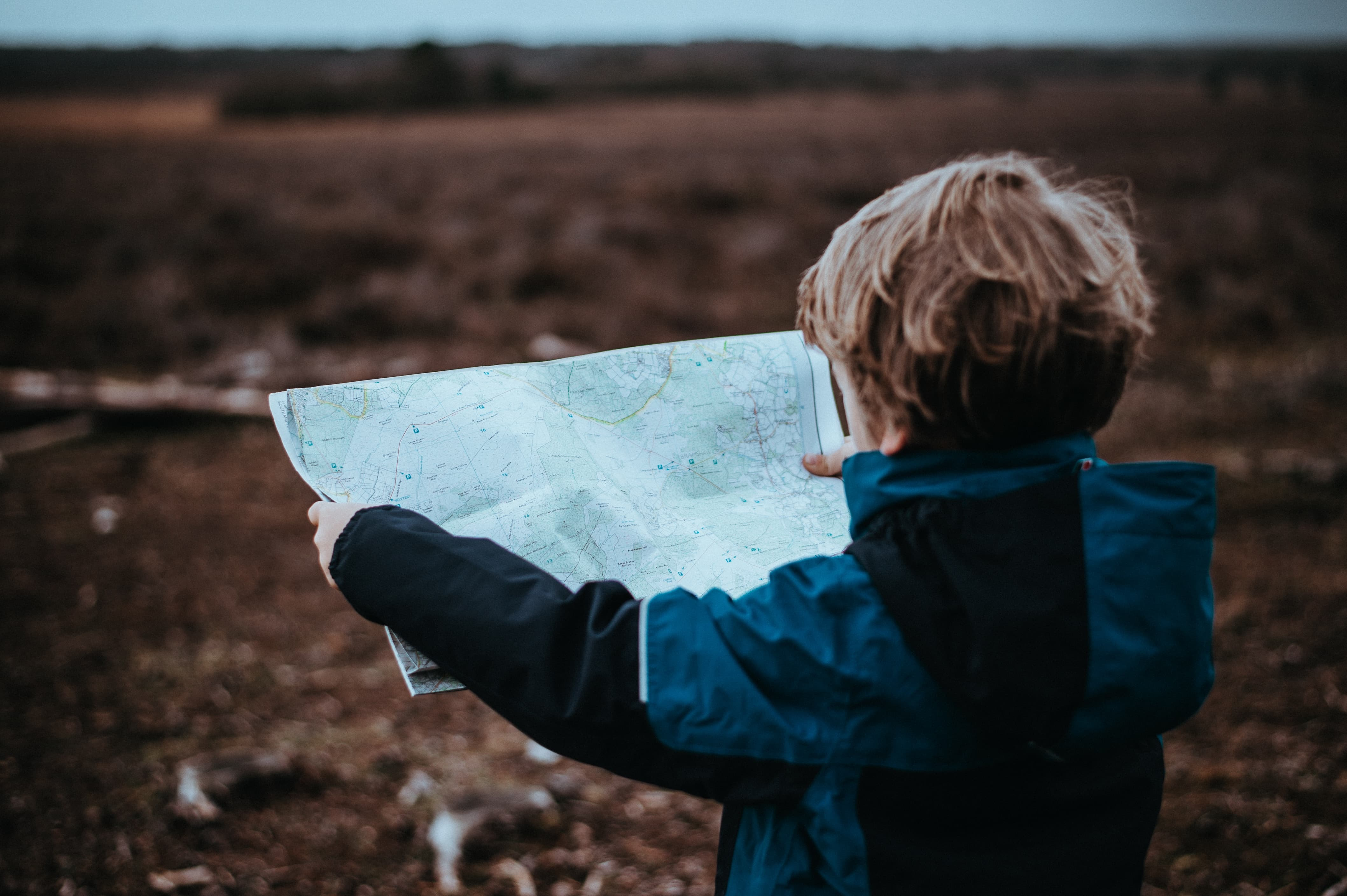 kid-looking-to-a-map-on-an-empty-field